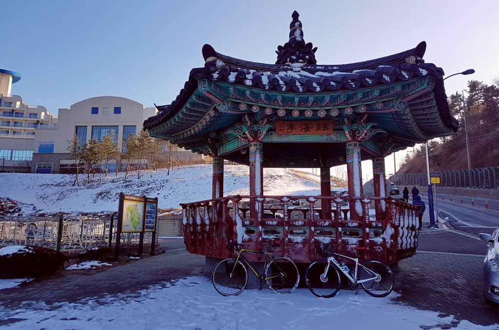 A picture of snow, bikes, and a pagoda.